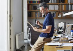 Side view of businessman using digital tablet while leaning on desk in office